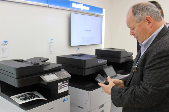 PrinterOn CEO Angus Cunningham uses a smartphone to manage a print job on a Samsung multifunction printer.