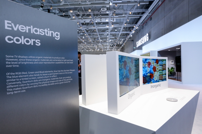 Visitors observe a frozen-image color durability comparison of a conventional screen and a Quantum Dot display.