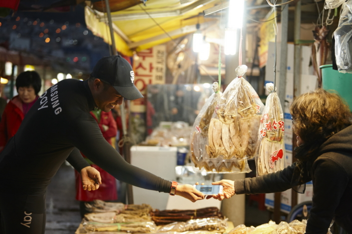 Derek Shimozawa uses Samsung Pay to make a purchase at a seafood market in Busan, Korea.